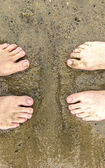Feet of father and son at the beach — Stock Photo