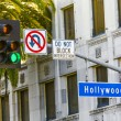 Hollywood Blvd street sign with tall palm trees. — Stock Photo