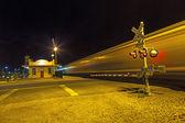 Treno passa all'incrocio della ferrovia nella notte — Foto Stock