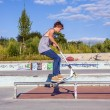 Boy has fun jumping with his scooter at the skate park — Stock Photo