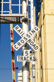 Railroad crossing sign with blue sky — Stock Photo