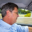 Happy man driving his car - Stock Photo