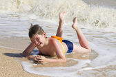 Boy lying on the beach in the surf — Stock Photo