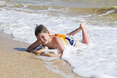 Boy lying on the beach in the surf — Stok fotoğraf
