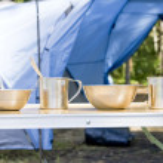 Tourist utensils near camping tent — Stock Photo