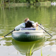 Green rubber inflatable boat with man — Stock Photo