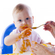 A young blue-eyed child feeding pumpkin puree — Stock Photo