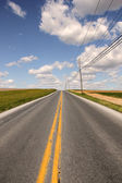 Country road to freedom with yellow line — Stock Photo
