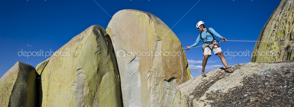 Climber rappelling from the summit of a rock spire after a challenging ascent.  Stock Photo #10984479