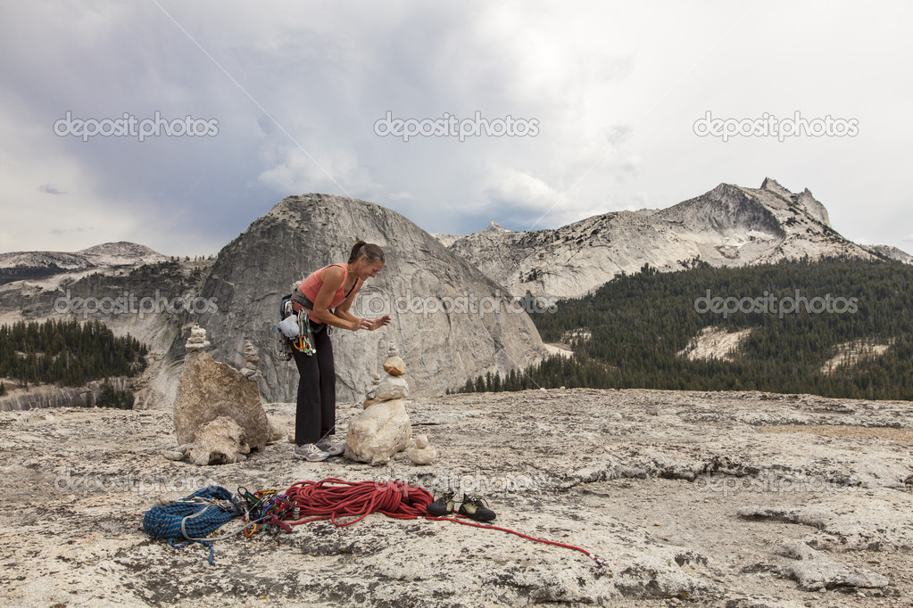 Climber stacks a stone monument on the summit after a challenging ascent. — Stock Photo #11686287