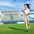 Girl running on football field — Stockfoto