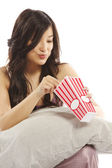 Young asian woman holding pillow eating popcorn — Stock Photo