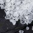 Coarse sea salt on black slate stone background, closeup - Stock Photo