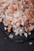 Coarse pink himalayan, sea salt on black slate stone background, — Stock Photo