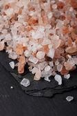 Coarse pink himalayan, sea salt on black slate stone background, — Stock Photo
