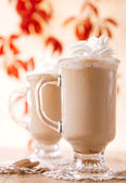 Coffee latte macchiato with cream in glasses on leaves backgroun — Stock Photo