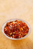 Hot Red Chilli Chillies pepper crushed in tin bowl on wood — Stock Photo
