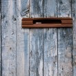 Very old postbox in wheathered wooden fence - Stock Photo