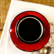 Black coffee, red enamel mug, two old silver spoons on embroider — Stock Photo #12347857