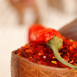 Stock Photo: red chillies paper in curved wooden bowl and camel caravan silh