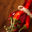 Red hot chillies pepper bunch in wooden bowl background — Stock Photo