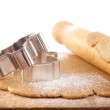 Christmas gingerbread cookie cutters on dough with rolling pin, — Stock Photo