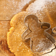 Gingerbread girl cookie cutter from above with dough on wood, ve — Stock Photo