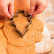 Little girl with  cutter make a christmas tree cookie — Stock Photo