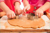 Little girls cutting gingerbread christmas cookies, hands only — Stock Photo