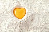 Love to bake it! egg yolk on flour, full frame — Stock Photo