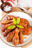 Homemade smoked chicken drumsticks and thighs on a plate — Stock Photo