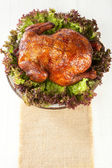 Homemade smoked whole chicken on leaf lettuce bed and plates — Stock Photo