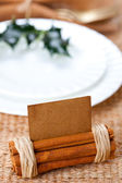 Aromatic place card with holly twig in white plate — Stock Photo