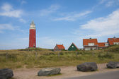 Red lighthouse, little houses and four stones on Texel island — Stock Photo
