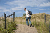 Young man with a backpack climbing up a hill — Stock Photo