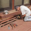Senior repairing wood deck — Stock Photo