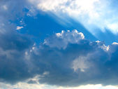 Blue sky with sun rays through the clouds — Стоковое фото