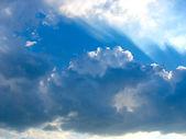 Blauwe lucht met stralen van de zon door de wolken — Stockfoto
