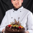 Handsome chef with cake — Stock Photo