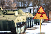 Radiation hazard sign with tanks — Stock Photo