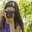 Young girl taking photos at summer green park — Stock Photo