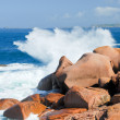 Stock Photo: Sea wave breaks against the pink granite rocks
