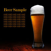Beer into glass on a black and wooden table — Stock Photo