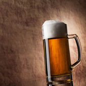 Beer into glass on a old stone — Stock Photo
