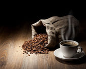 Coffee cup with burlap sack of roasted beans on rustic table — Stock Photo