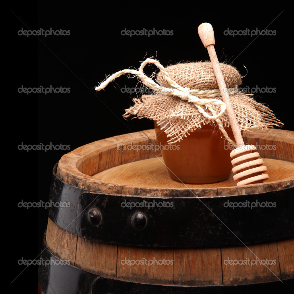 Honey pot and honey stick ona wooden barell  Stock Photo #11372748