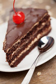 Slice of chocolate cake with cherry — Stock Photo