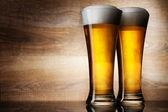 Iki bardak bira boşaltmak ahşap zemin üzerine — Stok fotoğraf
