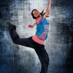 Modern style dancer posing behind studio background — Stock Photo