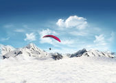 Mountain landscape with snow and man flying in the sky — Stock Photo